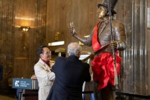 Kwan Wu and Keith Nelson cut the ribbon on the Francois Chouteau bronze sculpture at Kansas City, Missouri, City Hall.